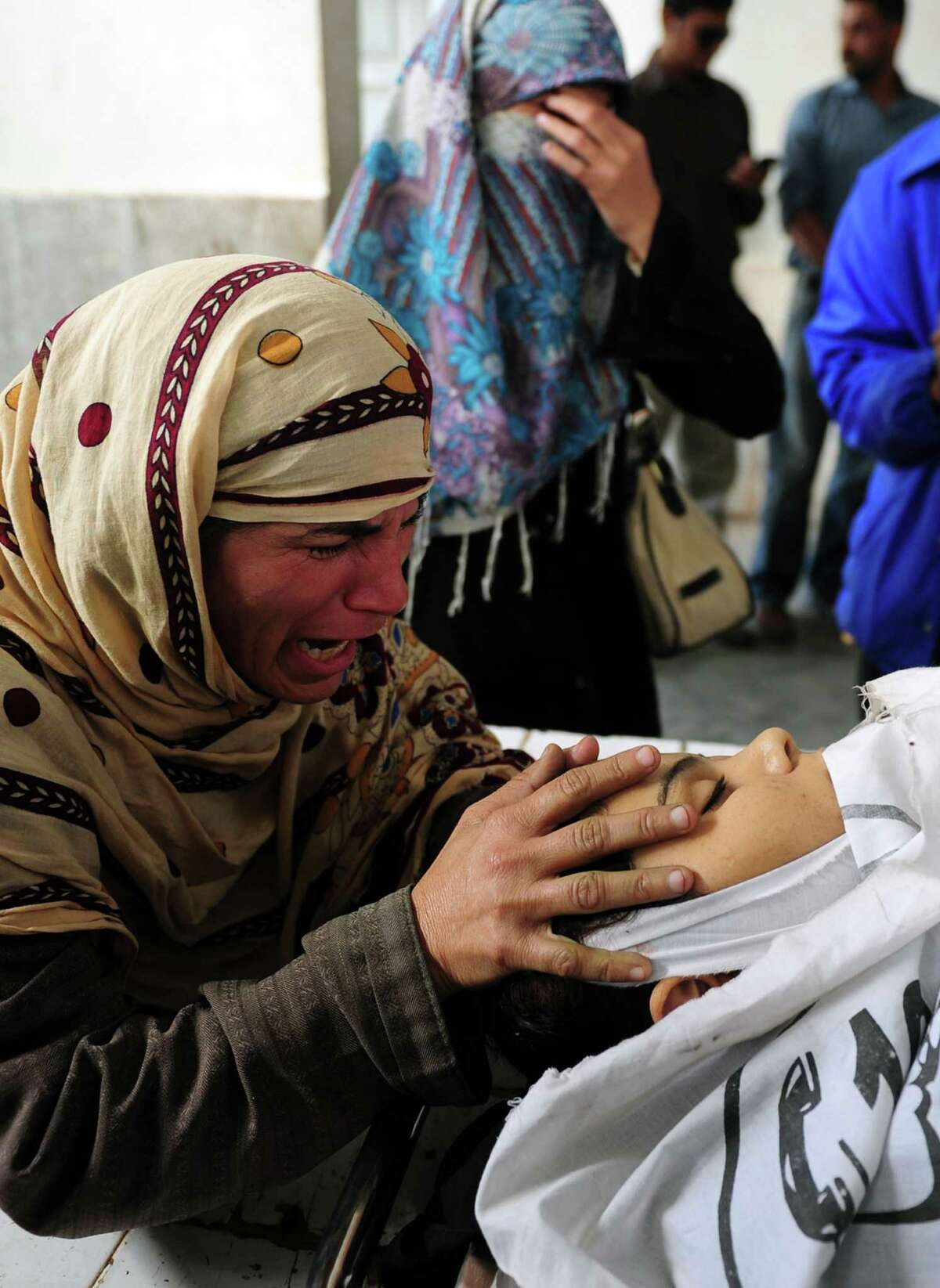 A Pakistani mother mourns over her daughter, who was killed while on the job as a polio vaccination worker, at a hospital morgue following an attack by gunmen in Karachi on December 18, 2012. Gunmen on motorbikes shot dead five female Pakistani polio vaccination workers on Tuesday, police said, highlighting resistance to the country's immunisation campaign. Four were killed in three different incidents in the sprawling port city and the fifth in the northwestern city of Peshawar, on the second day of a nationwide three-day drive against the disease, which is endemic in Pakistan. AFP PHOTO/Rizwan TABASSUMRIZWAN TABASSUM/AFP/Getty Images
