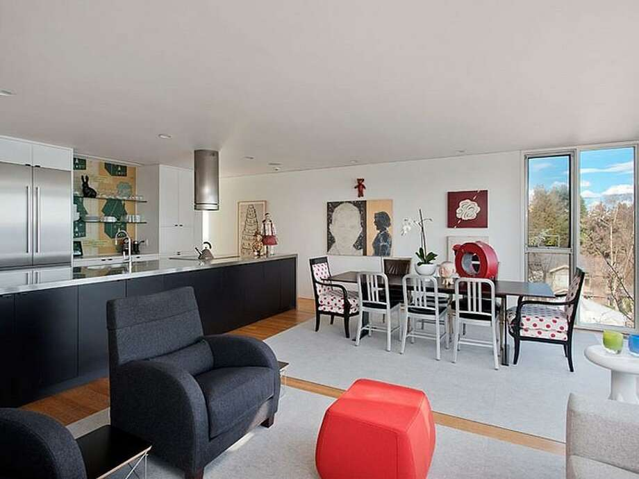 Main living area of 700 37th Ave. The 2,220-square-foot house, built in 1977, has two bedrooms, two three-quarter bathrooms, a lower-level rec room, walls of windows, a skylight, built-ins, a big deck and unobstructable views of Lake Washington, Bellevue and the Cascade Mountains. It's listed for $995,000. Photo: Courtesy Moira Holley And Scott Wasner/Realogics Sotheby's International Realty