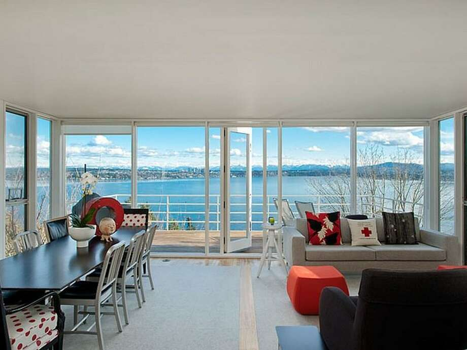 Living and dining rooms of 700 37th Ave. The 2,220-square-foot house, built in 1977, has two bedrooms, two three-quarter bathrooms, a lower-level rec room, walls of windows, a skylight, built-ins, a big deck and unobstructable views of Lake Washington, Bellevue and the Cascade Mountains. It's listed for $995,000. Photo: Courtesy Moira Holley And Scott Wasner/Realogics Sotheby's International Realty