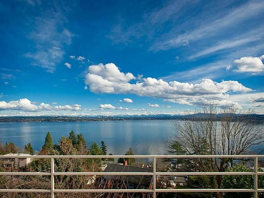 View from 700 37th Ave. The 2,220-square-foot house, built in 1977, has two bedrooms, two three-quarter bathrooms, a lower-level rec room, walls of windows, a skylight, built-ins, a big deck and unobstructable views of Lake Washington, Bellevue and the Cascade Mountains. It's listed for $995,000. Photo: Courtesy Moira Holley And Scott Wasner/Realogics Sotheby's International Realty