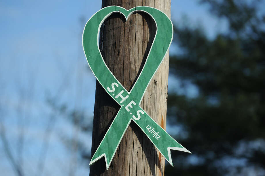 A large wooden ribbon in honor of Sandy Hook Elementary School hangs on a utility pole in Newotwn, Conn., Dec. 18th, 2012. Photo: Ned Gerard / Connecticut Post