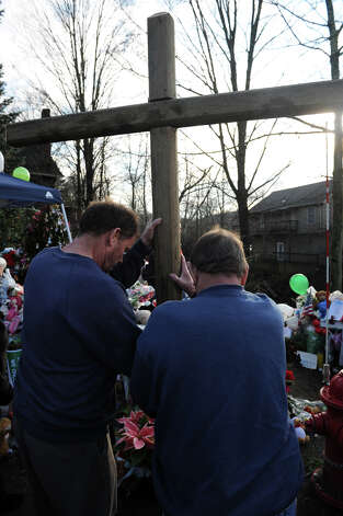 Jeff Fuller and his father Ray, of Newtown, sets up a wooden cross in front of a memorial at the main intersection at Sandy Hook, in Newtown, Conn., Dec. 18th, 2012. Memorial in Sandy Hook and Newtown continue to grow following last Friday's mass shooting at Sandy Hook Elementary School. Photo: Ned Gerard / Connecticut Post