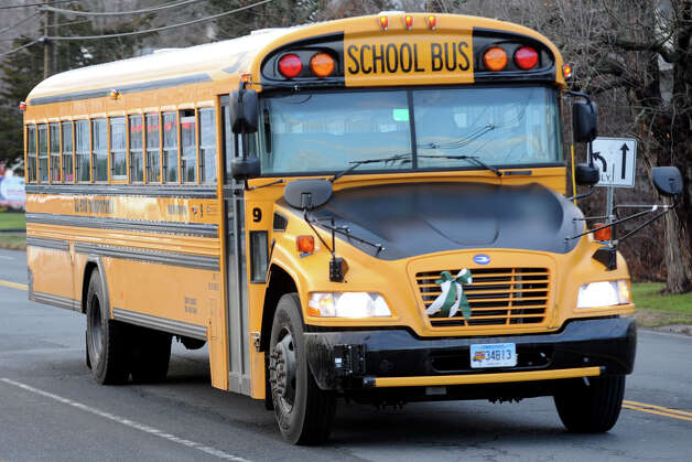 School buses in Newtown, Conn. are adorned with green and white ribbons, the Sandy Hook Elementary School colors, Dec. 18th, 2012. Tuesday was the first day the students went back to school following the mass shooting last Friday in Sandy Hool. Photo: Ned Gerard / Connecticut Post