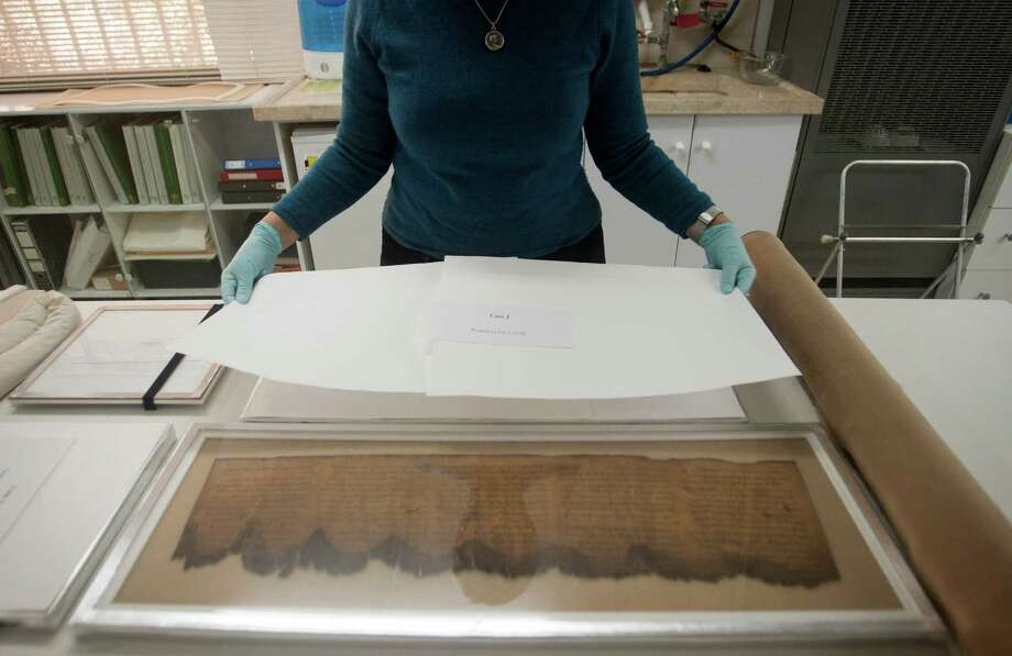 An Israel Antiquities Authority, IAA, worker presents fragments of the Dead Sea Scrolls, at the IAA offices at the Israel Museum in Jerusalem, Tuesday, Dec. 18, 2012. Israeli authorities say they have put 5,000 fragments of the ancient Dead Sea scrolls online in a partnership with Google.(AP Photo/Dan Balilty) Photo: Dan Balilty