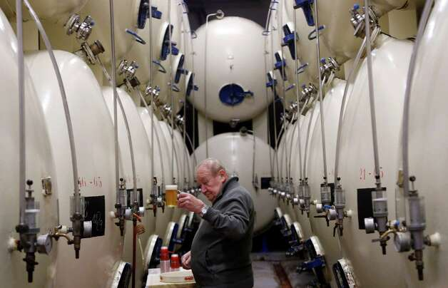 In this Tuesday, Oct. 30, 2012 photo, a brewer checks a glass of beer at the Budejovicky Budvar brewery  in Ceske Budejovice, Czech Republic. They've been arguing about a name for 106 years. A small brewer in the Czech Republic and the world's biggest beer maker have been suing each other over the right to put the word Budweiser on their bottles in what has become a David versus Goliath corporate saga. A deal, it seems, will have to wait a bit longer because settlement talks between state-owned Budejovicky Budvar and Anheuser-Busch, a U.S. company now part of AB InBev, have collapsed, according to Budvar's director general, Jiri Bocek. (AP Photo/Petr David Josek) Photo: Petr David Josek