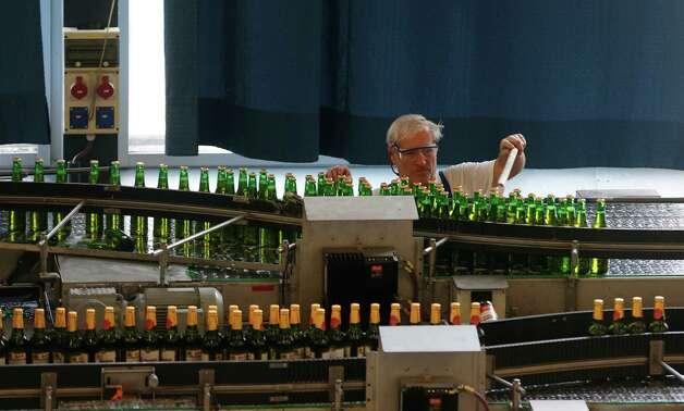 In this Tuesday, Oct. 30, 2012 photo a worker examines a line of bottles of beer, at the Budejovicky Budvar brewery, in Ceske Budejovice, Czech Republic. They've been arguing about a name for 106 years. A small brewer in the Czech Republic and the world's biggest beer maker have been suing each other over the right to put the word Budweiser on their bottles in what has become a David versus Goliath corporate saga. A deal, it seems, will have to wait a bit longer because settlement talks between state-owned Budejovicky Budvar and Anheuser-Busch, a U.S. company now part of AB InBev, have collapsed, according to Budvar's director general, Jiri Bocek. (AP Photo / Petr David Josek) Photo: Petr David Josek