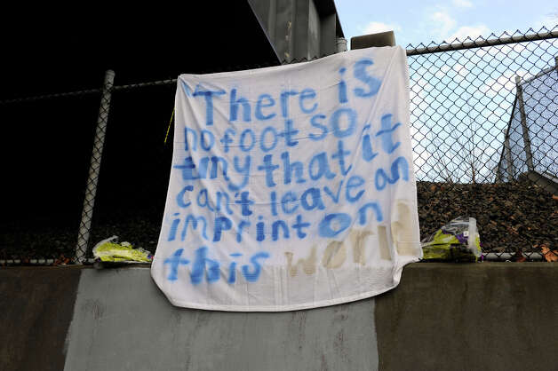This sign hangs under a railroad overpass on Church Hill Rd. In Newtown Tuesday, Dec. 18, 2012. There are many signs and memorials in Newtown in honor of the 26 victims of the Sandy Hook Elementary School shooting on Friday. Photo: Carol Kaliff / The News-Times