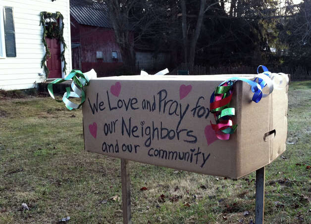 "Newtown residents who live across from the Botsford Post Office were moved to place this sign of support for the community in front of their home. ""Our hearts are broken,"" it says. ""We pray for our neighbors. We love you, we hug you."" Photo: Linda Koonz / The News-Times"
