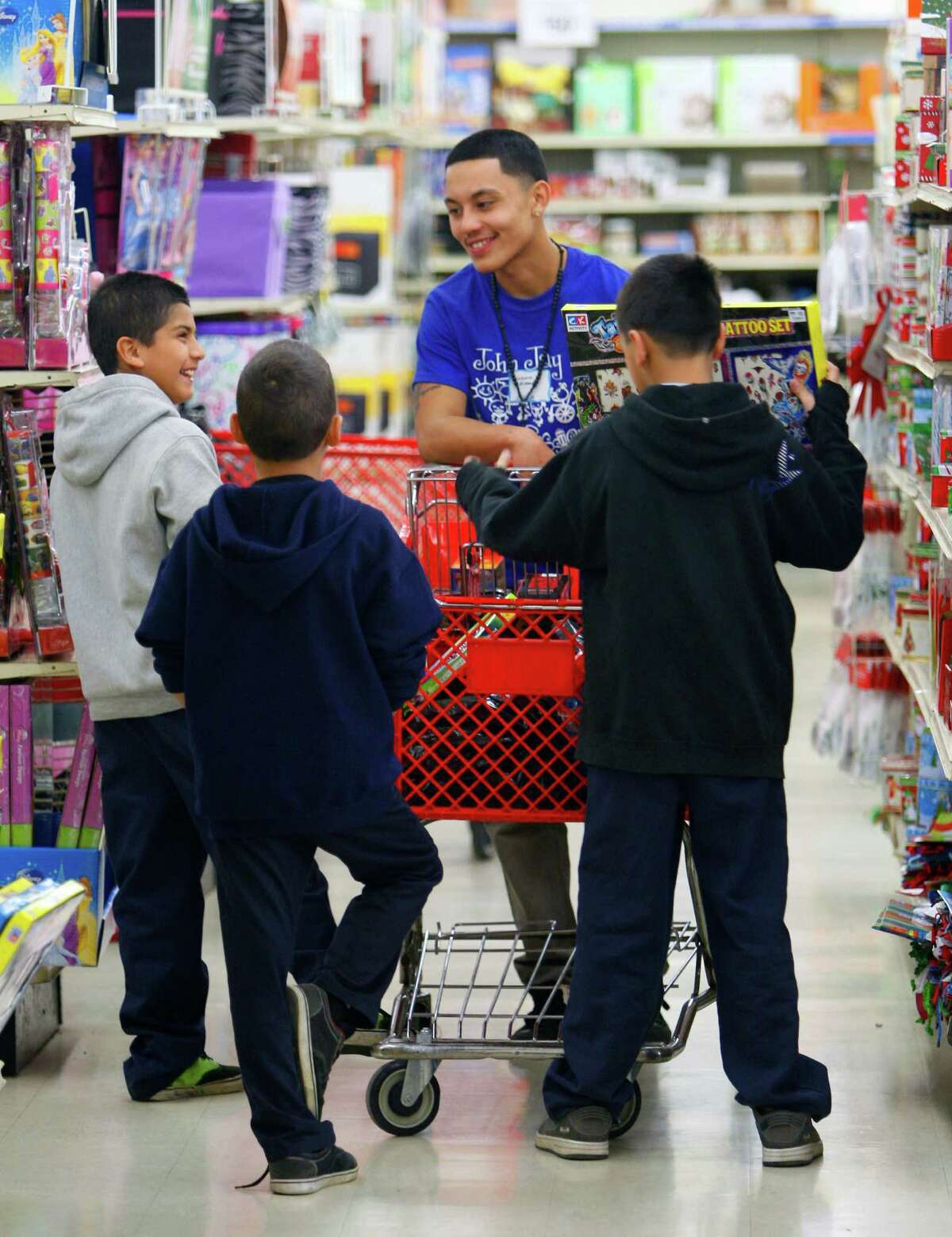 Lazaro Alvarado, facing camera, from John Jay High School, helps elementary students Oscar Cruz, from left, Adrian Marsh, and Aries Marsh Tuesday Dec. 18, 2012, pick out toys. Jay High School students, who raised about $7,000 for the giveaway, helped students pick out $25 worth of toys and a pair of shoes costing up to $25.