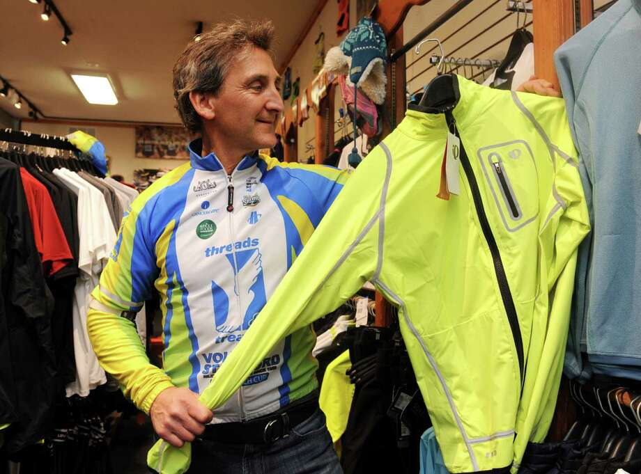 Mickey Yardis, owner of Threads & Treads on East Putnam Avenue in Greenwich, Conn., wears a colorful jacket for cycling Tuesday, Dec. 18, 2012. Yardis sells bicycle safety equipment for sale at the store, including brightly colored riding clothes and blinking lights. Greenwich police each year deal with up to a dozen motor vehicle/bike accidents on town roads. Both police and cycling enthusiasts say safety education and sharing the road are key to limiting those accidents. Photo: Helen Neafsey / Greenwich Time