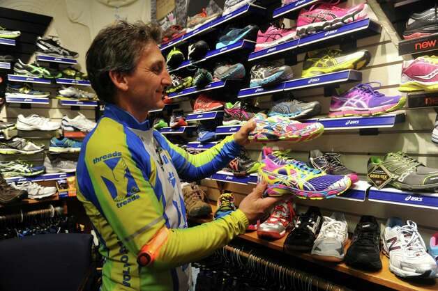 Mickey Yardis, owner of Threads & Treads on East Putnam Avenue in Greenwich, Conn., displays colorful sneakers for cycling Tuesday, Dec. 18, 2012. Yardis sells bicycle safety equipment for sale at the store, including brightly colored riding clothes and blinking lights. Greenwich police each year deal with up to a dozen motor vehicle/bike accidents on town roads. Both police and cycling enthusiasts say safety education and sharing the road are key to limiting those accidents. Photo: Helen Neafsey / Greenwich Time