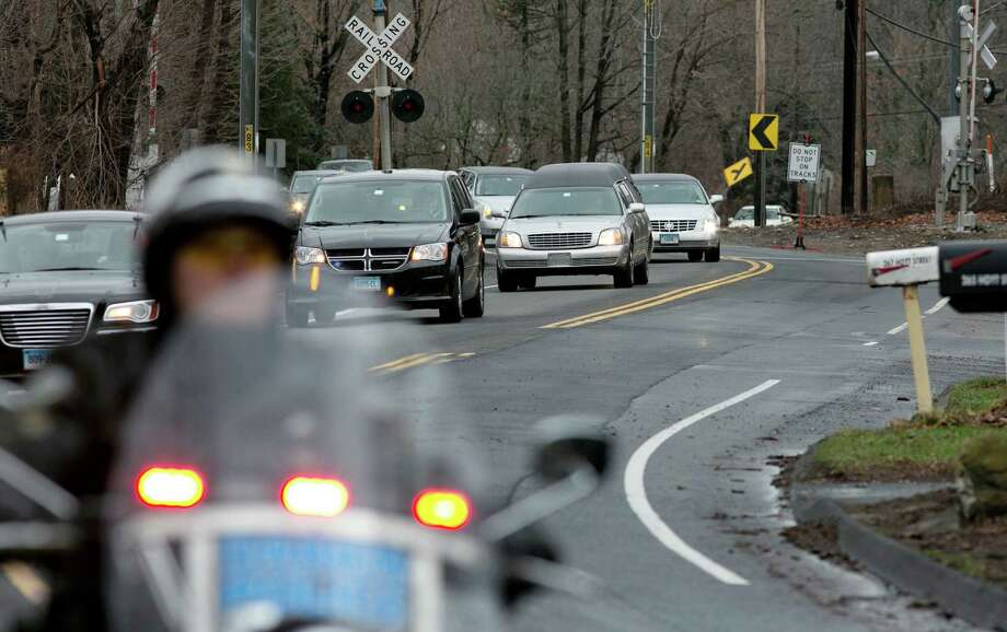 The funeral procession for James Mattioli, 6, who died in the Sandy Hook Elementary School shootings, approaches the St. John's Cemetery Tuesday, Dec. 18, 2012, in Darien, Conn. Gunman Adam Lanza walked into Sandy Hook Elementary School in Newtown, Dec. 14,  and opened fire, killing 26 people, including 20 children. (AP Photo/Craig Ruttle) Photo: Craig Ruttle, AP / FR61802 AP