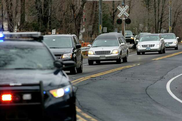 The funeral procession for James Mattioli, 6, who died in the Sandy Hook Elementary School shootings, approaches the St. John's Cemetery Tuesday, Dec. 18, 2012, in Darien, Conn. A gunman walked into Sandy Hook Elementary School in Newtown, Dec. 14,  and opened fire, killing 26 people, including 20 children. Tuesday, Dec. 18, 2012. (AP Photo/Craig Ruttle) Photo: Craig Ruttle, AP / FR61802 AP