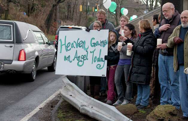 Friends and co-workers hold a sign as the hearse and funeral procession for James Mattioli, 6, who died in the Sandy Hook Elementary School shootings, approaches the St. John's Cemetery Tuesday, Dec. 18, 2012, in Darien, Conn. Tuesday, Dec. 18, 2012. (AP Photo/Craig Ruttle) Photo: Craig Ruttle, AP / FR61802 AP