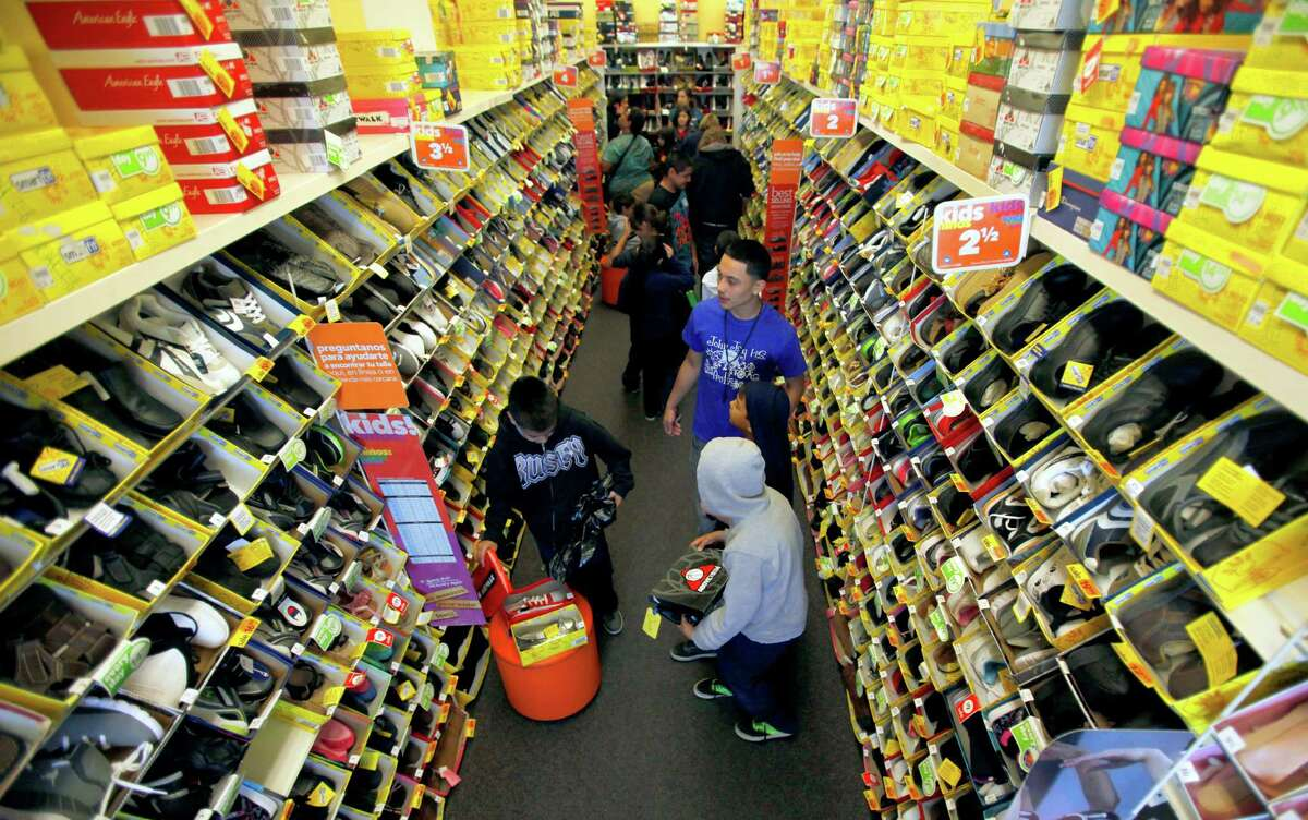 Lazaro Alvarado, back right in blue shirt, from John Jay High School, helps elementary students Aries Marsh, Adrian Marsh, and Oscar Cruz Tuesday Dec. 18, 2012 pick out shoes. Jay High School students, who raised about $7,000 for the giveaway, helped students pick out $25 worth of toys and a pair of shoes costing up to $25