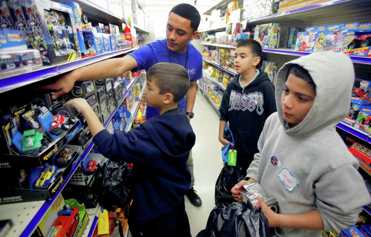 Lazaro Alvarado, back left, from John Jay High School, helps elementary students Adrian Marsh, from left, Aries Marsh, and Oscar Cruz, Tuesday Dec. 18, 2012, pick out toys. Jay High School students, who raised about $7,000 for the giveaway, helped students pick out $25 worth of toys and a pair of shoes costing up to $25.