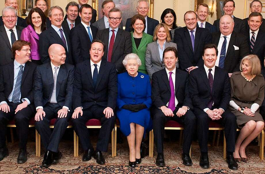 Queen Elizabeth sits between Prime Minister David Cameron (left) and Deputy Prime Minister Nick Clegg as she poses for a picture with the Cabinet. Photo: Jeremy Selwyn, AFP/Getty Images