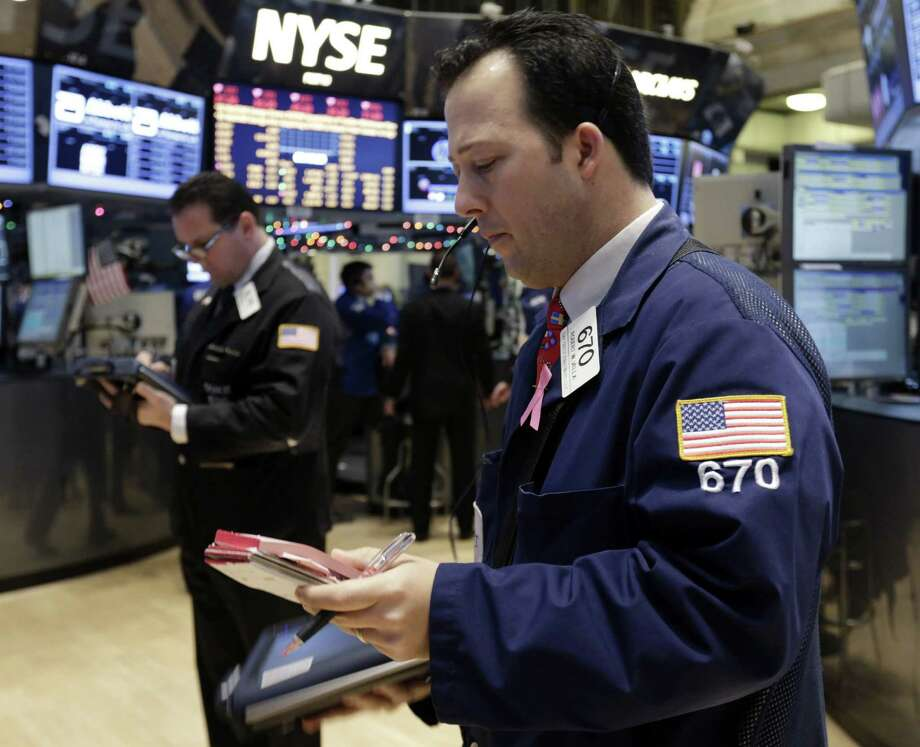 """In this Friday, Dec. 14, 2012, photo, trader Robert Vella, right, works on the floor of the New York Stock Exchange. Stocks edged higher on Wall Street amid optimism that the lawmakers in Washington are closing in on a budget deal that will stop the U.S. going over the """"fiscal cliff.""""  (AP Photo/Richard Drew) Photo: Richard Drew"""