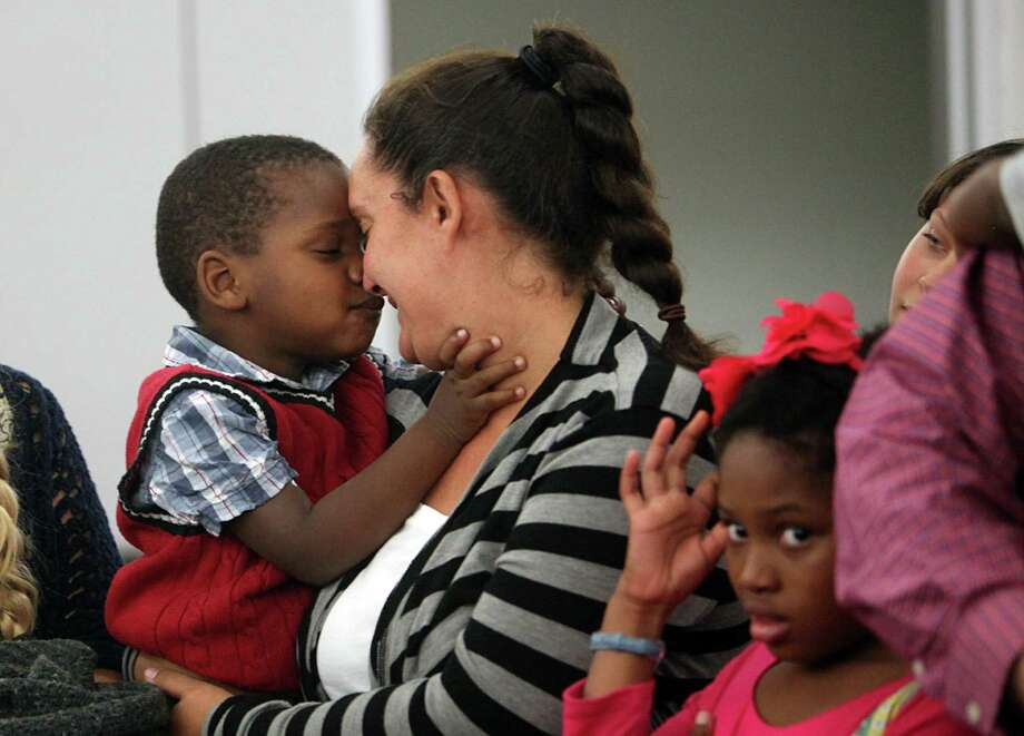 "John Valor Haight, 3, caresses his mother Charity Haight, during the adoption ceremony in 315th court at the Juvenile Justice Center on Tuesday, Dec. 18, 2012, in Houston. Over 90 CPS children, ages 1-17, have found their ""forever home"" for Christmas. They were part of a mass adoption celebration. Photo: Mayra Beltran, Houston Chronicle / © 2012 Houston Chronicle"