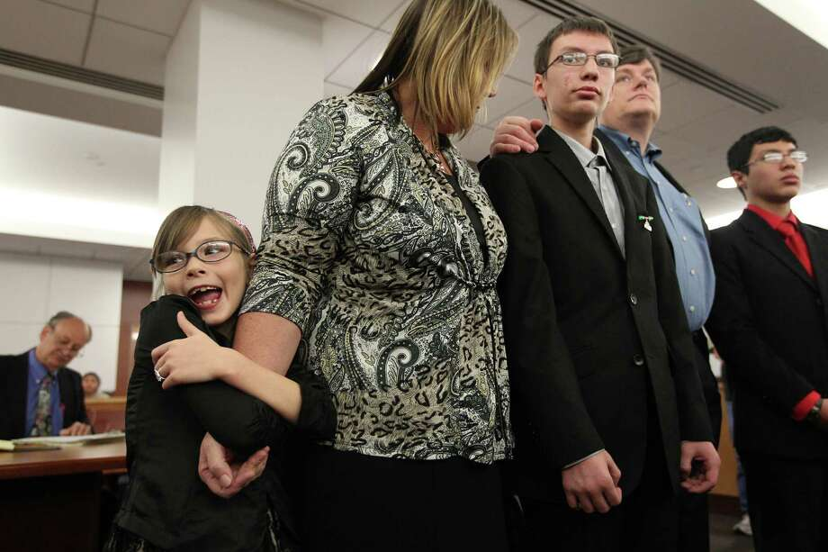 "Angelina Gallagher, 8, clamps to her mother Ann Marie Gallagher in excitement during the adoption ceremony for her and bother (center) Wesley Gallagher, 16, in court 315th at the Juvenile Justice Center on Tuesday, Dec. 18, 2012, in Houston. Over 90 CPS children, ages 1-17, have found their ""forever home"" for Christmas, and were part of a mass adoption celebration. Photo: Mayra Beltran, Houston Chronicle / © 2012 Houston Chronicle"