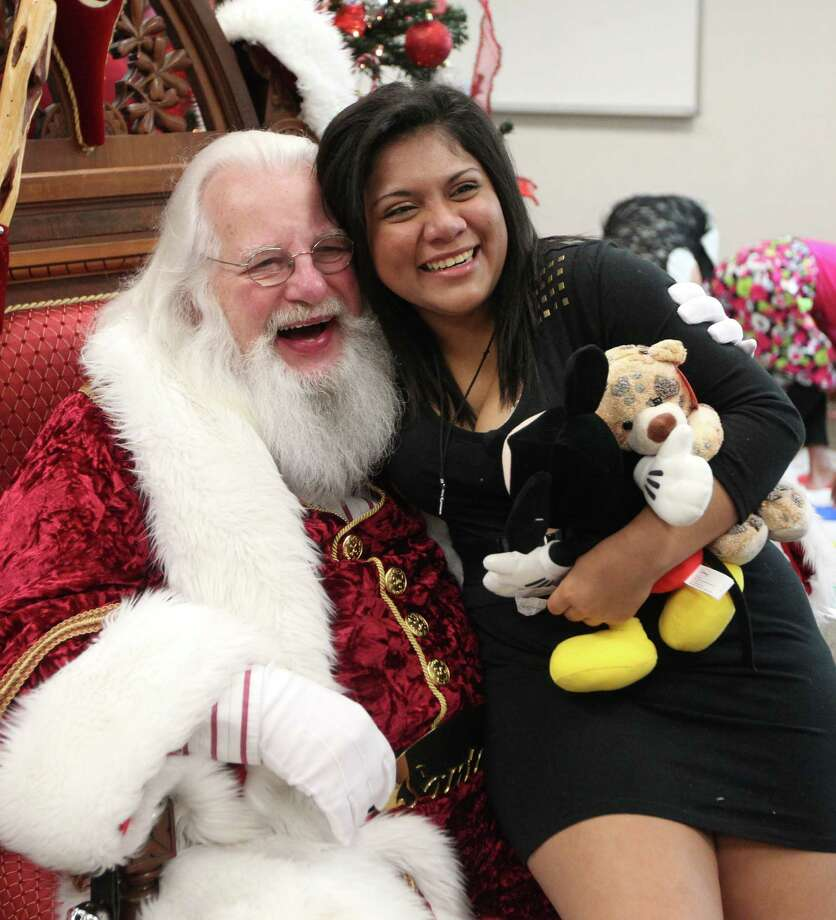 "Santa gives a hug to Desiree Ivey, 16, in the celebration adoption celebration at the Juvenile Justice Center on Tuesday, Dec. 18, 2012, in Houston. Over 90 CPS children, ages 1-17, have found their ""forever home"" for Christmas, and were part of a mass adoption celebration. Photo: Mayra Beltran, Houston Chronicle / © 2012 Houston Chronicle"