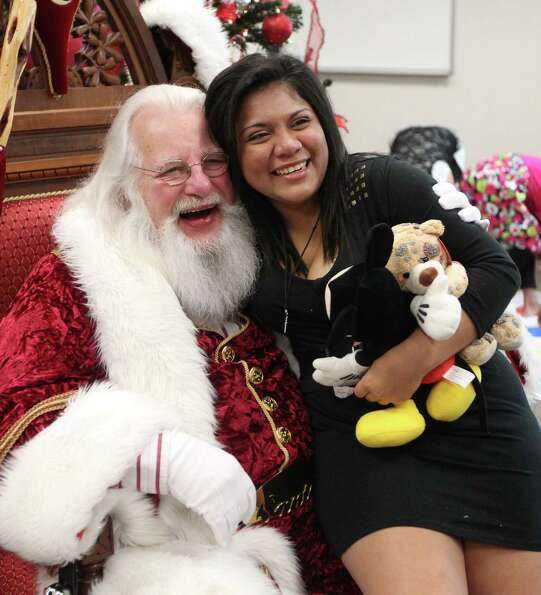 Santa gives a hug to Desiree Ivey, 16, in the celebration adoption celebration at the Juvenile Justi
