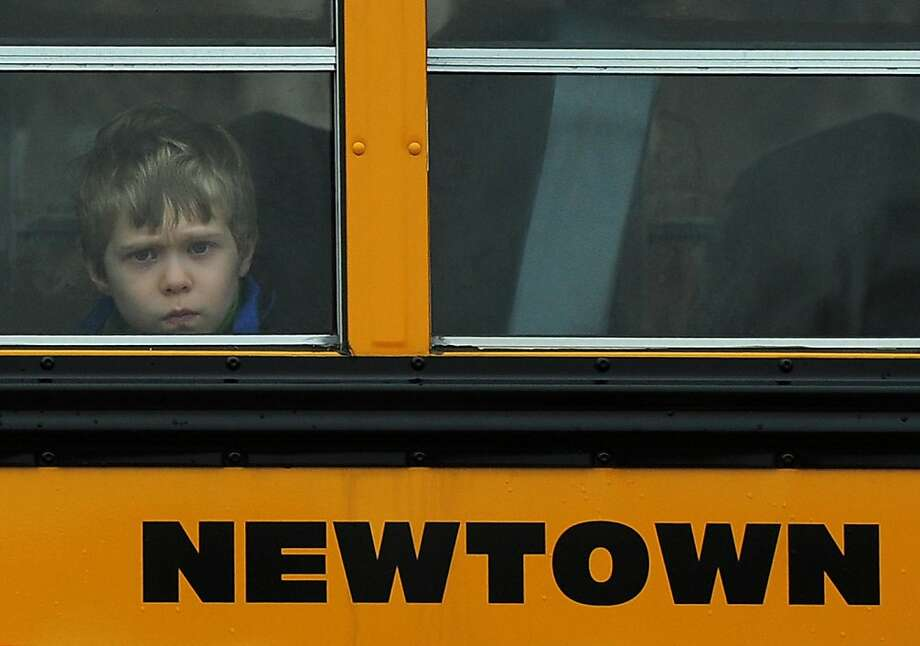 A child looks out of a bus window as it passes by Saint Rose of Lima Church where the funeral of James Mattioli, 6 is taking place on December 18, 2012 in Newtown, Connecticut. Most children in Newtown returned to classes for the first time since last week's massacre, but survivors of the shooting stayed at home and their school remained a crime scene. In a thin drizzle, yellow school buses once again rolled through the Connecticut town, where some 5,400 children are enrolled. Photo: Emmanuel Dunand, AFP/Getty Images