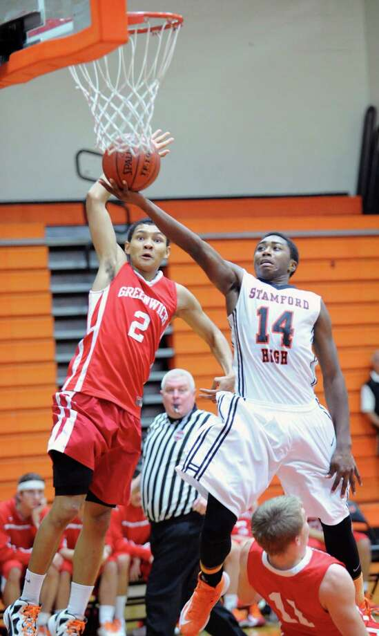 At left, CJ Byrd (# 2) of Greenwich blocks the layup attempt of Kenny Wright (# 14) of Stamford during the 2nd quarter of the boys high school basketball game between Greenwich High School and Stamford High School at Stamford, Tuesday night, Dec. 18, 2012. Greenwich beat Stamford, 46-44. Photo: Bob Luckey / Greenwich Time