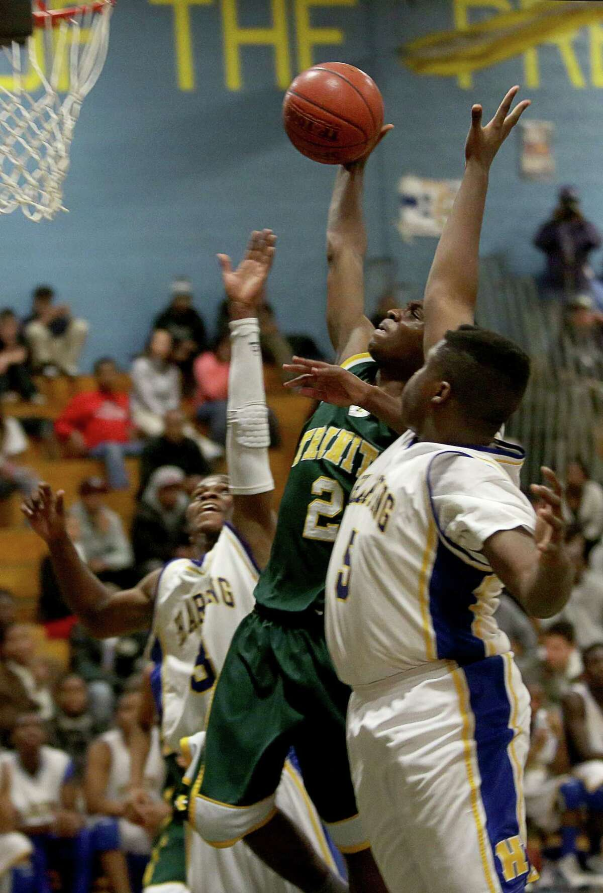 Mike Ross Connecticut Post freelance -Trinity Catholic's # 2 Schadrac Casimir goes to the hoop against Harding High School's # 3 Terrence Rogers and # 5 Jamar (last name not on roster) during Tuesday evening match in Bridgeport.