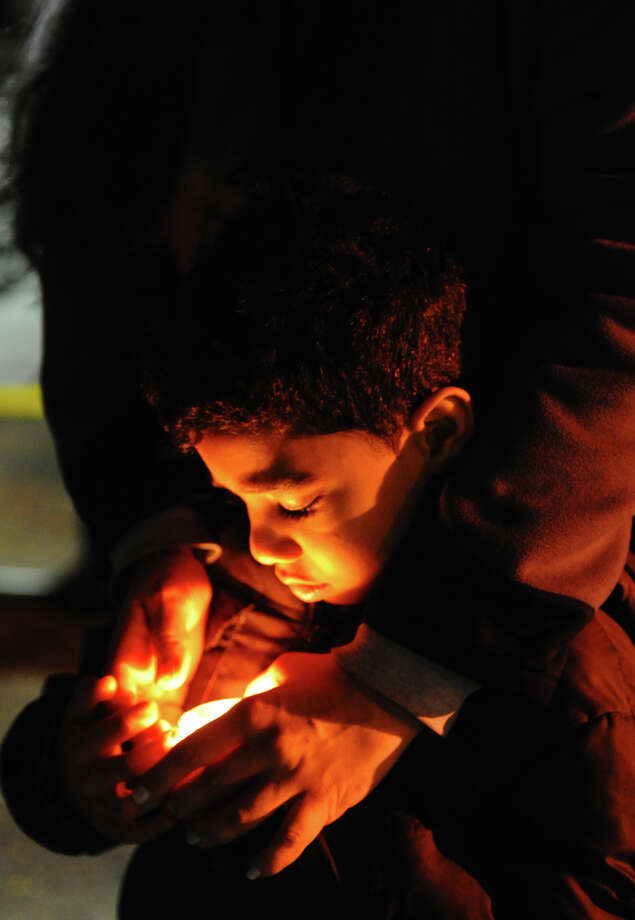 Nasiz Dean, 5, hellps hold a candle with his mom Victoria, during a candlelight vigil held to remember the Newtown massacre victims at Norwalk Community College in Norwalk, Conn. on Tuesday December 18, 2012. Photo: Christian Abraham / Connecticut Post