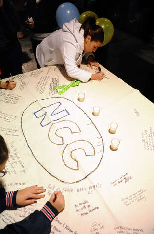 Student Paula Castaneda signs a memorial poster, during a candlelight vigil held to remember the Newtown massacre victims at Norwalk Community College in Norwalk, Conn. on Tuesday December 18, 2012. Photo: Christian Abraham / Connecticut Post