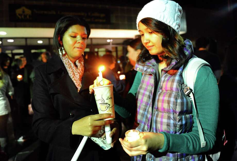 Students Deanna Fields, left, and Aygul Gara-Dashly take part in a candlelight vigil held to remember the Newtown massacre victims at Norwalk Community College in Norwalk, Conn. on Tuesday December 18, 2012. Photo: Christian Abraham / Connecticut Post