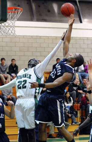 Norwalk's #22 Roy Kane and Staples #23 Darryle Wiggins, right, reach for a rebound, during boys basketball action against Staples in Norwalk, Conn. on Tuesday December 18, 2012. Photo: Christian Abraham / Connecticut Post