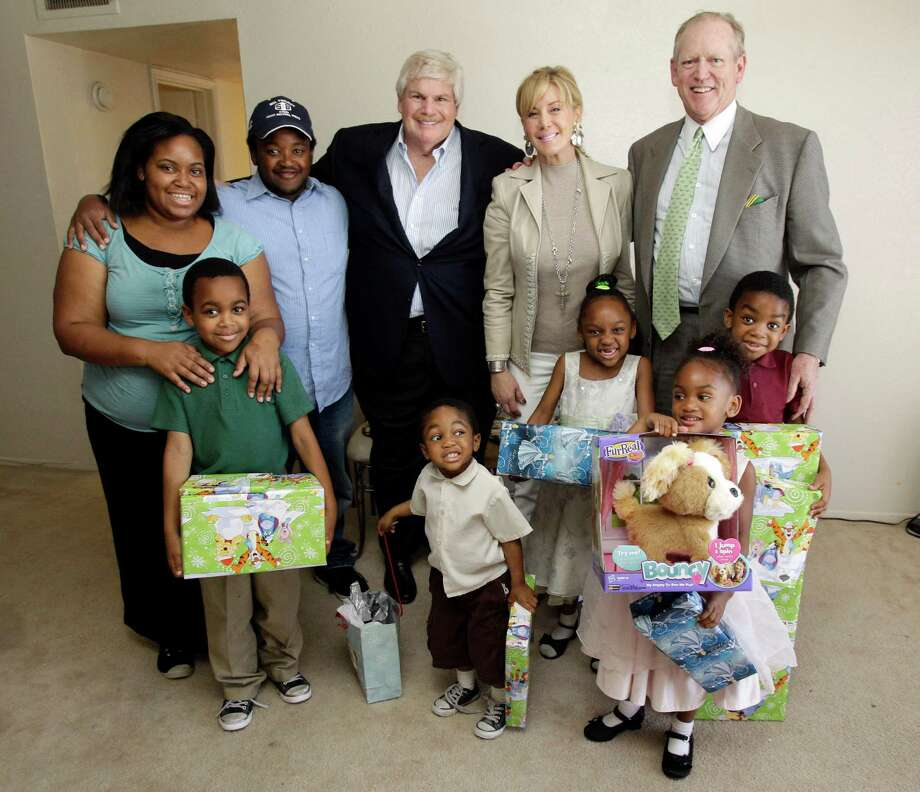 LaShawn McCorkle, front left, Josiah, Maaliyah, Amiela and Evon join their parents, Bryanna and Kenneth McCorkle, along with Goodfellows donors John Eddie Williams Jr. and his wife, Sheridan, and Houston Chronicle Chairman Jack Sweeney, right. Photo: Melissa Phillip, Staff / © 2012 Houston Chronicle
