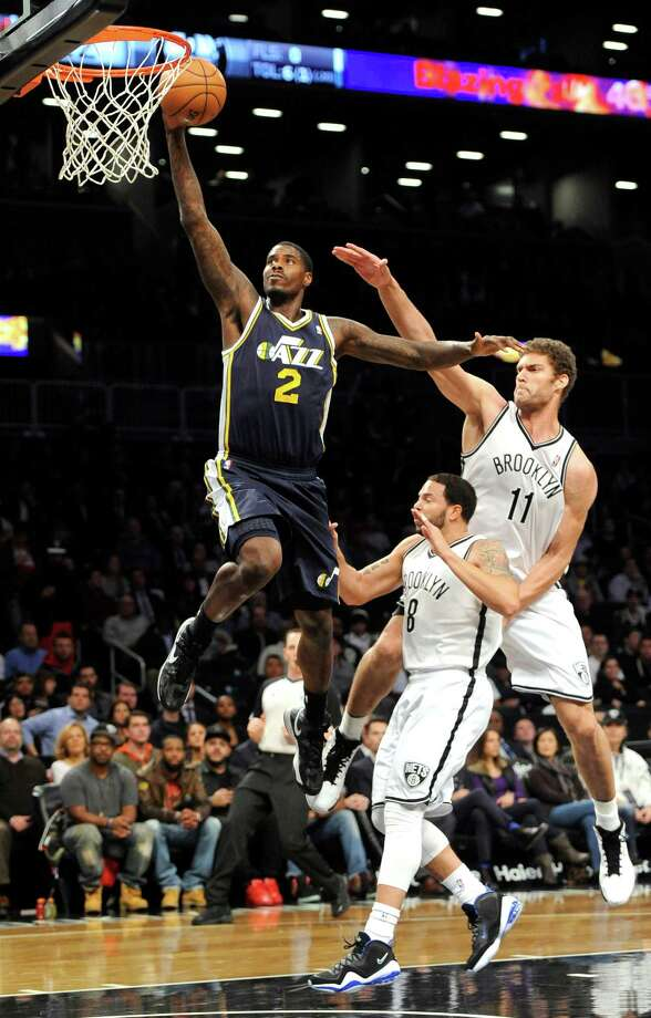 Utah Jazz's Marvin Williams (2) drives to the basket in front of Brooklyn Nets' Deron Williams (8) and Brook Lopez (11) in the first half of an NBA basketball game, Tuesday, Dec. 18, 2012, at Barclays Center in New York. (AP Photo/Kathy Kmonicek) Photo: Kathy Kmonicek