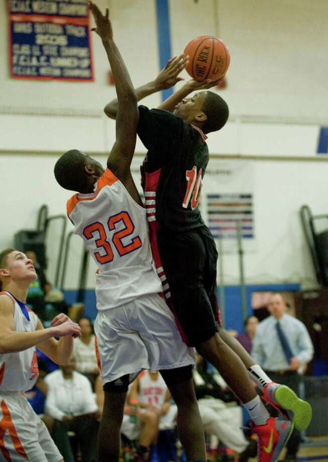 Danbury High School's Jalen McCallen tries to block the shot of Bridgeport Central High School's Shaawen Bretox in a game at Danbury. Tuesday, Dec. 18, 2012 Photo: Scott Mullin / The News-Times Freelance