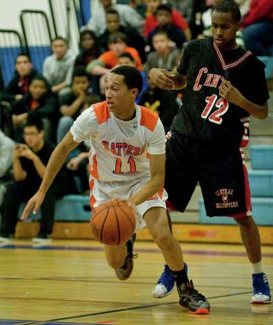 Danbury High School's Marquise Marrero moves the ball away from Bridgeport Central High School's Ricky Grant in a game at Danbury. Tuesday, Dec. 18, 2012 Photo: Scott Mullin / The News-Times Freelance