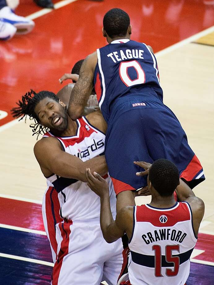Hawks point guard Jeff Teague charges into Wizards center Nene for an offensive foul late in the second half. Atlanta won 100-95 in overtime. Photo: Harry E. Walker, McClatchy-Tribune News Service