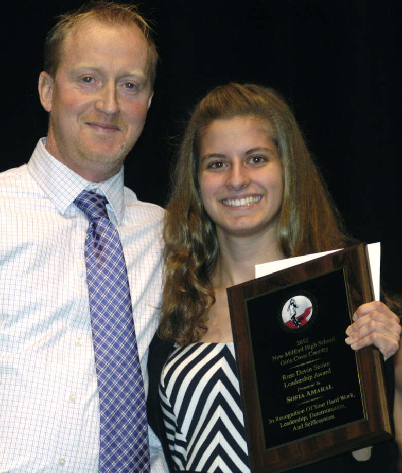 Green Wave girls cross country's Sofia Amaral is presented by coach Giles Vaughan with the inaugural Russell Devin Senior Leadership Award, given in memory of the legendary NMHS educator and track and cross country coach during the New Milford High School fall sports awards ceremony, Dec. 10, 2012 Photo: Norm Cummings