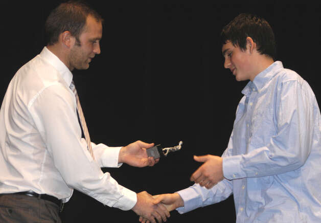 Green Wave boys' soccer coach Antony Howard presents is team's MIP award to Nevan Swanson during the New Milford High School fall sports awards ceremony, Dec. 10, 2012 Photo: Norm Cummings
