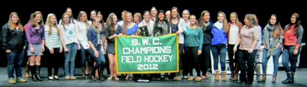 The Green Wave field hockey squad displays its South-West Conference title banner during the New Milford High School fall sports awards ceremony, Dec. 10, 2012 Photo: Norm Cummings