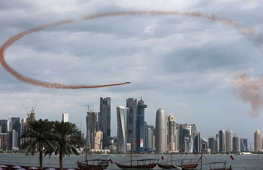 A Qatari fighter jet flies over skyscrapers during the Gulf emirate's National Day celebrations in Doha on December 18, 2012. Photo: Karim Jaafar, AFP/Getty Images
