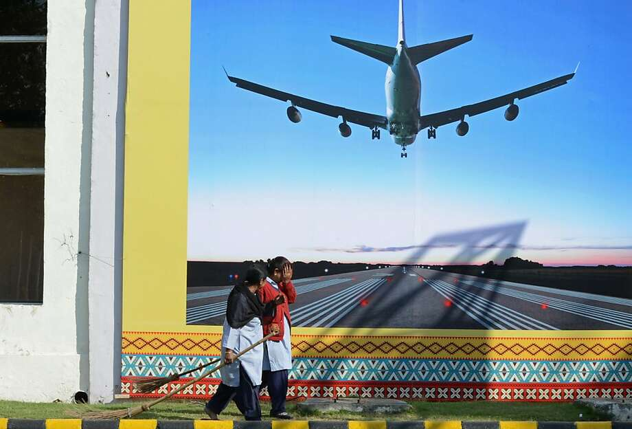 Indian sweepers walk past a billboard of an aircraft on final approach outside the venue of the 2nd India-ASEAN Business Fair and Business Conclave in New Delhi on December 18, 2012. Trade and commerce ministers from ten ASEAN countries are attending the two-day conference. Photo: Raveedran, AFP/Getty Images