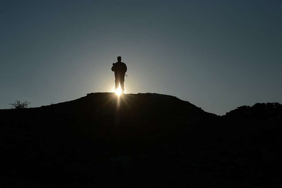 """An Afghan commando force stand guard at sunset in Goshti district of Nangarhar province, bordering  Pakistan on December 18, 2012.The Afghan security forces, which did not exist until the Taliban fell in 2001, have been built up quickly and still lack professionalism. According to a recent Pentagon report, Afghans have """"begun to assume the lead for security"""" in areas home to roughly 76 percent of the population. Between March and September, the United States decreased its military forces in Afghanistan by 25 percent. There are now about 68,000 US troops in the country. Photo: Shah Marai, AFP/Getty Images"""