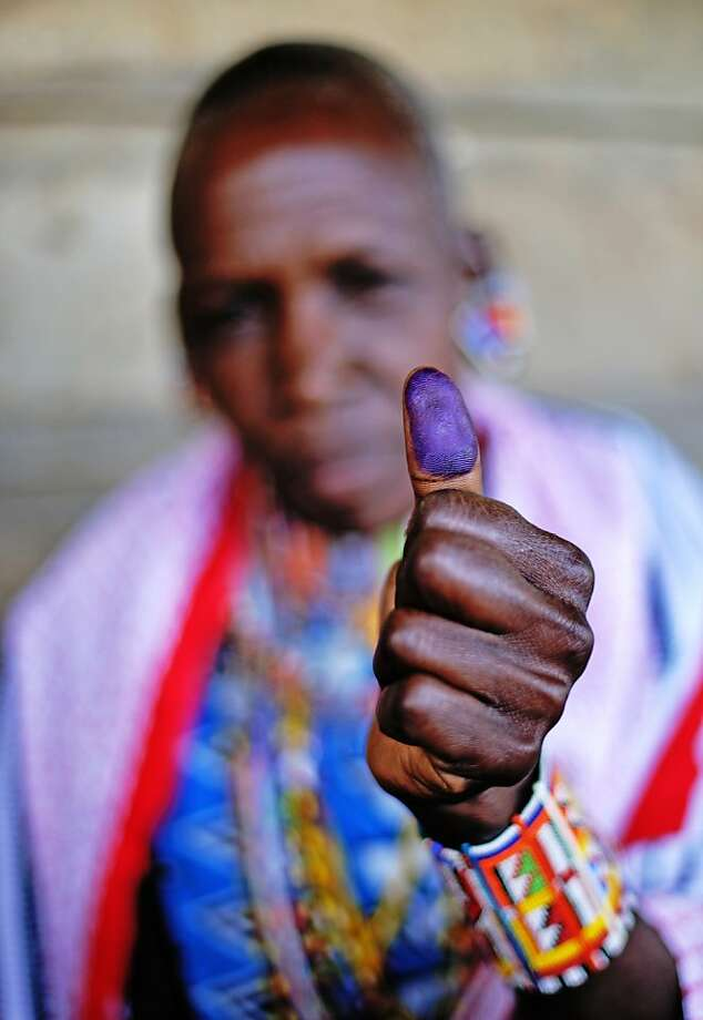 A Maasai woman presents her ink marked thumb after registering to vote in the general elections scheduled for March 2013 in the village of Olgumi in Kajiado County West on December 18, 2012. Today marked the last day for Kenyans to register to vote and voter registration centres across the country saw a marked increase in attendance of voters who were desperate to register at the last minute. The Independent Electoral and Boundaries Commission (IEBC) has taken biometric computer equipment to populations in remote tribal areas in order to ensure that the chance of voting fraud is decreased for the country's forthcoming elections. Photo: Carl De Souza, AFP/Getty Images