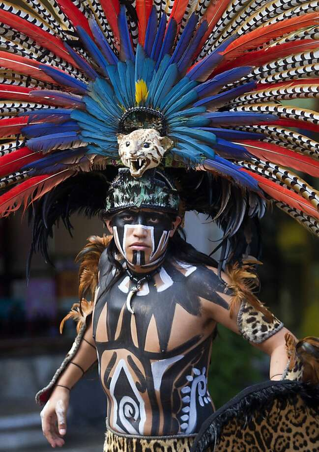 A Mexican man wearing a pre-hispanic costume performs at a tourist area of Playa del Carmen in Quintana Roo state, Mexico, on December 18, 2012, during preparations for the celebration of the end of the Maya Long Count Calendar --Baktun 13-- and the beginnig of a new era. Photo: Pedro Pardo, AFP/Getty Images