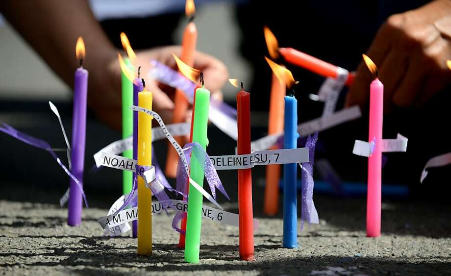 Members of human rights group, Volunteers Against Crime and Corruption (VACC), light candles with names of those killed during the shooting at Sandy Hook Elementary School in Newtown, Connecticut in the US, during a prayer vigil in front of the US Embassy in Manila on December 18, 2012.  Twenty children and six adults were reportedly killed by Adam Lanza, after he entered the school and opened fire. The massacre was the second-deadliest school shooting in the US after the 2007 Virginia Tech shooting. Photo: Noel Celis, AFP/Getty Images