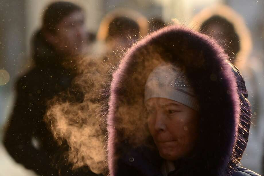 Moscovites try to stay warmas temperatures drop to 3 degrees Fahrenheit. Due to high humidity and a strong wind, weather experts said it would feel more like 13 below. Photo: Kirill Kudryatsev, AFP/Getty Images