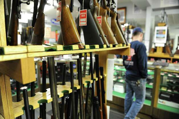 A customer looks at guns in Taylor & Vadney Sporting Goods Store on Tuesday Dec. 18, 2012 in Rotterdam, N.Y. (Lori Van Buren / Times Union) Photo: Lori Van Buren