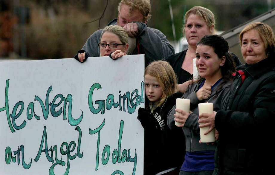 Tom Doyle, back left, standing with family and co-workers, wipes his face as the funeral procession for James Mattioli, 6, who died in the Sandy Hook Elementary School shootings, approaches the St. John's Cemetery Tuesday, Dec. 18, 2012, in Darien, Conn. Center are his wife Debbie and daughter Emily, 10. Adam Lanza opened fire Sandy Hook Elementary School in Newtown on Friday, killing 26 people, including 20 children.  (AP Photo/Craig Ruttle) Photo: Craig Ruttle